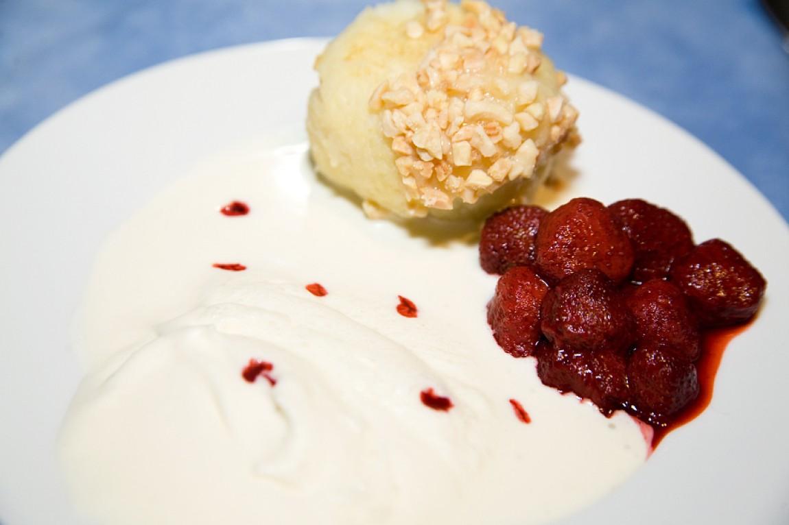 Kartoffelknöddel überzogen mit weißer Schokolade und kandierten Mandeln mit Erdbeeren und Vanillesauce